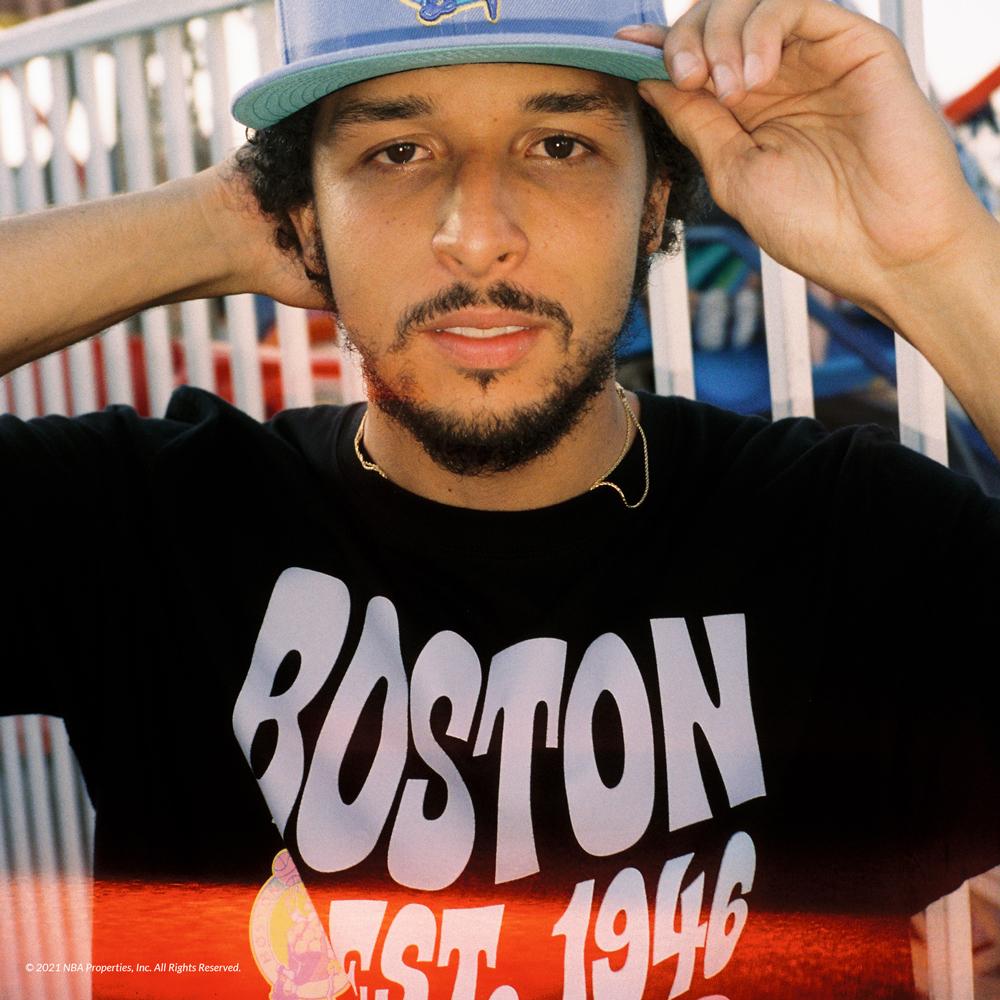 Man wearing Boston Celtics cap in front of ferris wheel