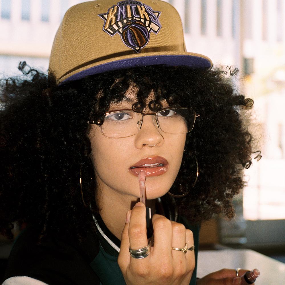 Woman wearing Knicks hat and applying lipstick